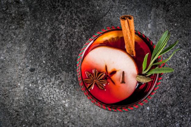 Boissons traditionnelles d'hiver et d'automne. cocktails de noël et de thanksgiving. vin chaud à l'orange, la pomme, le romarin, la cannelle et les épices