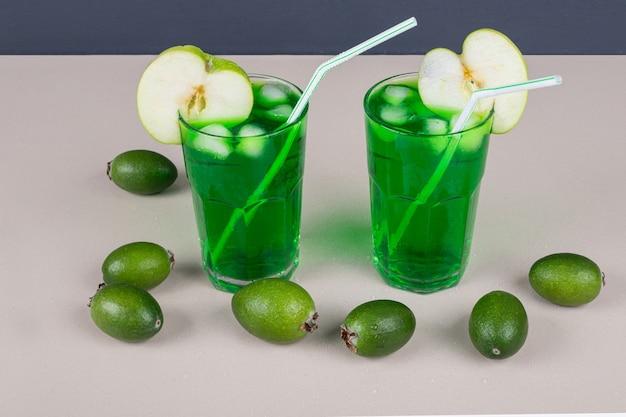 Boissons vertes à la pomme, feijoa et paille sur blanc