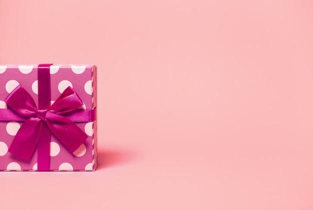 Boîte actuelle à pois enveloppée de ruban brillant sur coloré. thème festif et vacances.