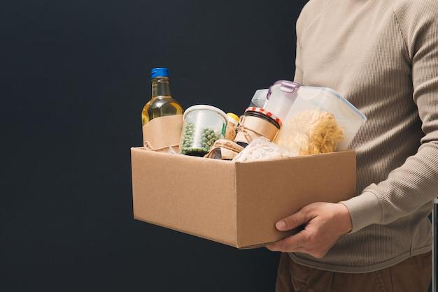Boîte d'aide aux dons pleine de fournitures. bénévole dans les gants de protection médicale tenant la boîte de nourriture pour la charité de livraison