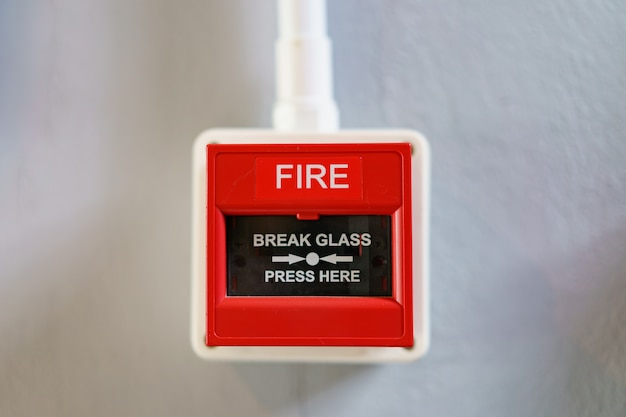 Boîte d'alarme incendie rouge sur fond blanc.