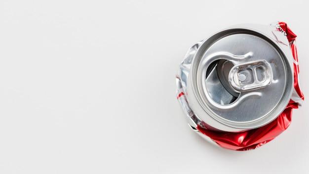 Boîte en aluminium aplatie placée sur un fond gris