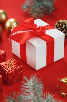 Boîte avec un arc rouge autour des décorations de noël sur fond rouge