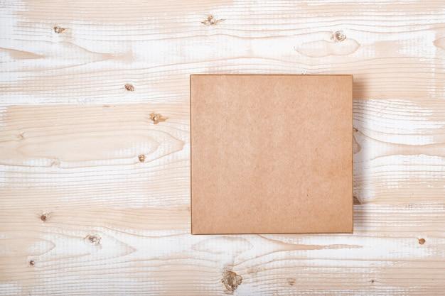Boîte artisanale carrée sur une table en bois blanc minable