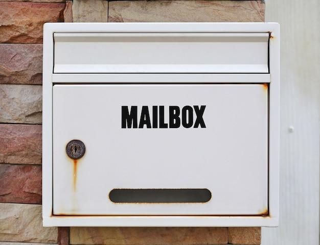 Boîte aux lettres blanche montée sur un mur de pierre