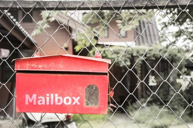 Boîte aux lettres rouge sur la clôture