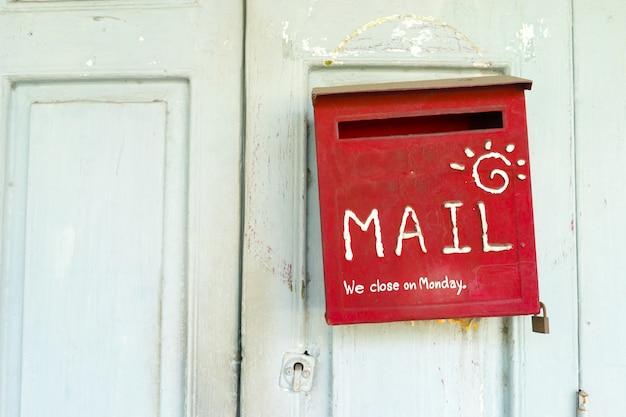 Boîte aux lettres rouge sur une porte en bois