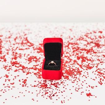 Boîte à bijoux avec bague près de confettis