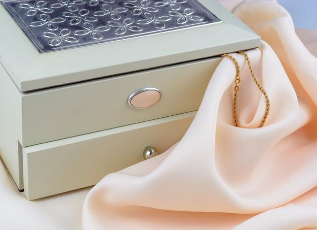 Boîte à bijoux avec bijoux sur fond textile en soie