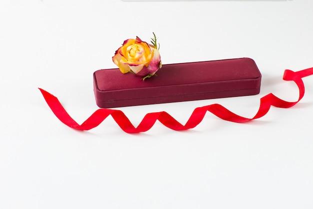 Boîte à bijoux, bouton de rose et ruban rouge