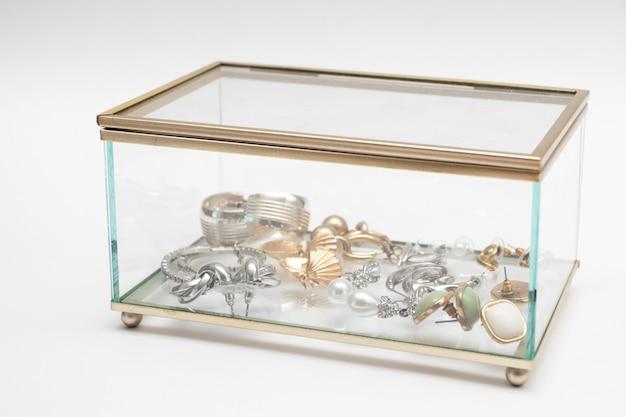 Boîte à bijoux décorative en verre avec des bijoux en or.