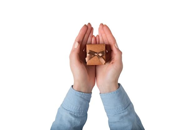 Boîte à bijoux marron en mains féminines. cadeau. isoler