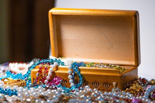 Boîte à bijoux, perles de nacre et divers autres bijoux multicolores, mise au point sélective, concept de prospérité