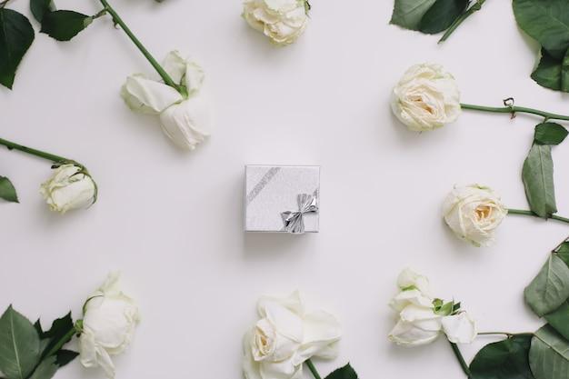 Boîte à bijoux et roses blanches sur blanc