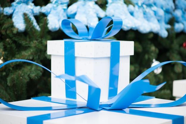 Boîte blanche avec cadeau du nouvel an et ruban bleu