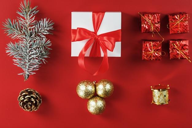 Boîte blanche avec un cadeau et un noeud rouge, autour de décorations de noël avec des branches de sapin sur un mur rouge. vue de dessus
