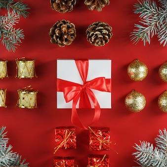 Boîte blanche de cadeau de nouvel an avec noeud rouge autour des décorations de noël sur fond rouge