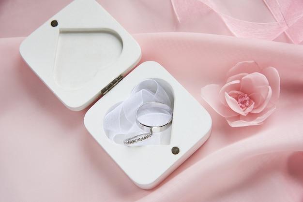 Boîte blanche pour alliances sur mousseline rose