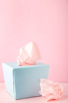 Boîte bleue avec des mouchoirs en papier et des serviettes froissées utilisées