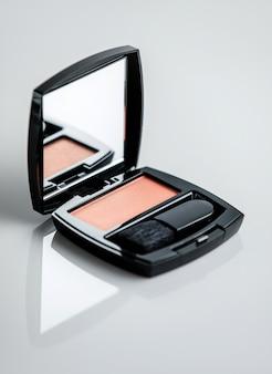 Une boîte de blush vue de face avec brosse et petit miroir sur la surface blanche