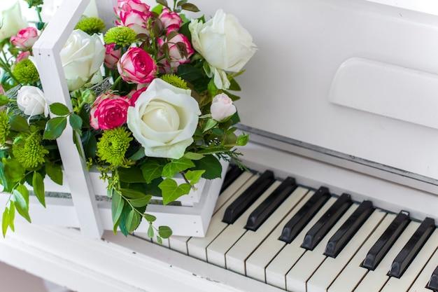 Boîte en bois blanche avec bouquet de roses blanches et roses et chrysanthèmes sur piano blanc. décoration de la maison. boîtes à fleurs. décoration de mariage