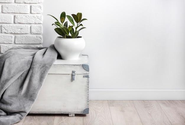 Boîte en bois blanche avec une jeune plante en caoutchouc dans un pot de fleur blanc et une couverture polaire douce grise dessus. mur blanc avec des briques sur fond