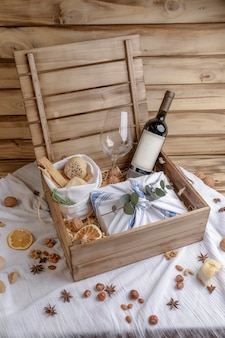 Boîte en bois de cadeau de noël avec de la nourriture, du pain et du vin rouge.