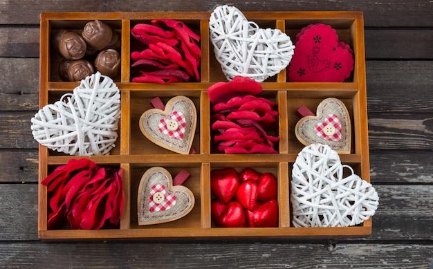 Une boîte en bois avec des coeurs, des bonbons, des pétales de rose