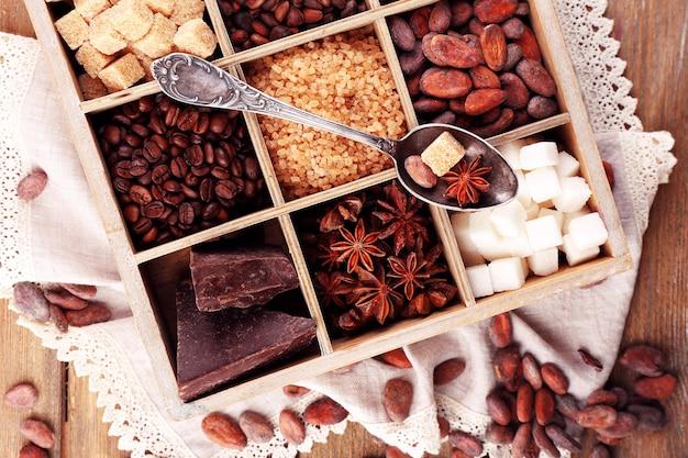 Boîte en bois avec ensemble de grains de café et de cacao, cubes de sucre, chocolat noir, cannelle et anis, gros plan, sur une surface en bois