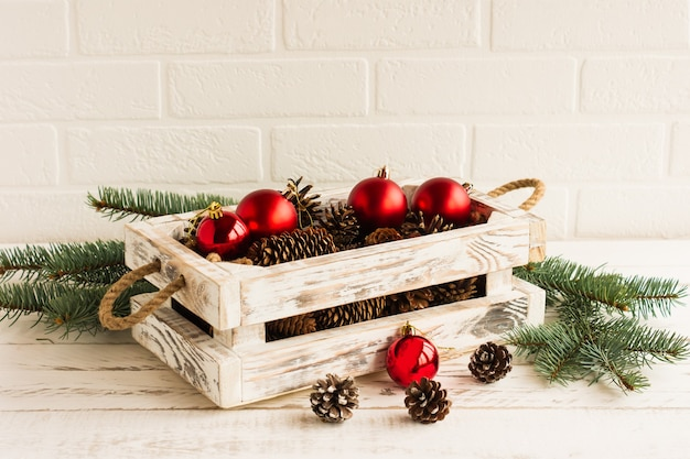 Une boîte en bois faite à la main blanche avec des boules de noël rouges et des branches d'épinette avec des cônes sur une table en bois.