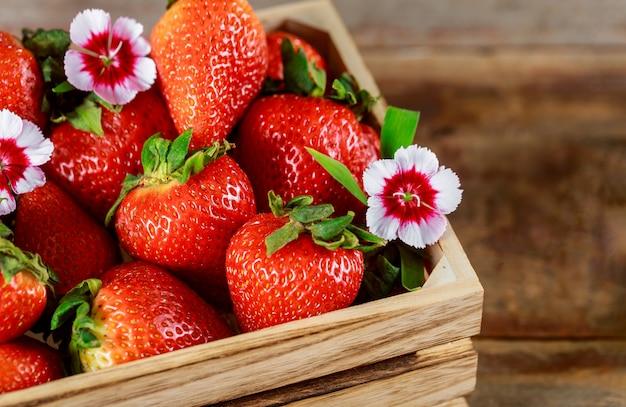 Boîte en bois de fraises rouges mûres fraîches sur un marché de producteurs