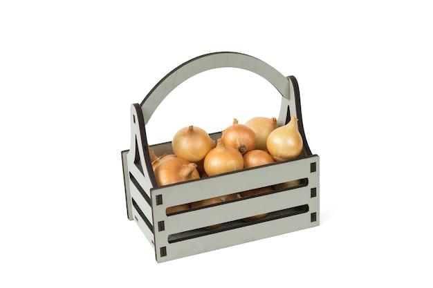 Boîte en bois grise avec des oignons frais isolés sur fond blanc.
