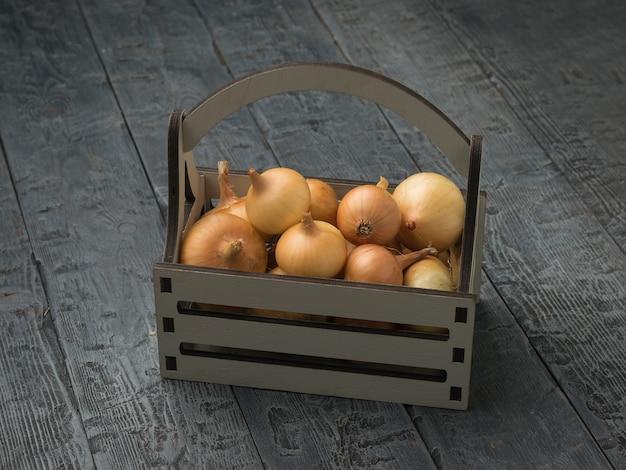 Une boîte en bois grise remplie de bulbes frais sur une table en bois.