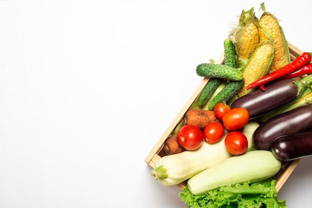 Boîte en bois avec des légumes frais sur fond blanc.