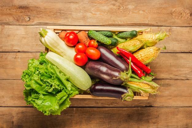 Boîte en bois avec des légumes frais sur un fond en bois.