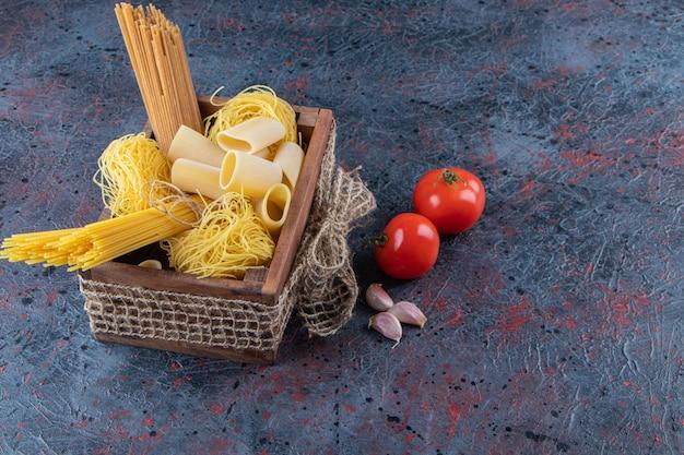 Une boîte en bois de nouilles crues avec des tomates rouges fraîches et de l'ail sur une surface sombre .