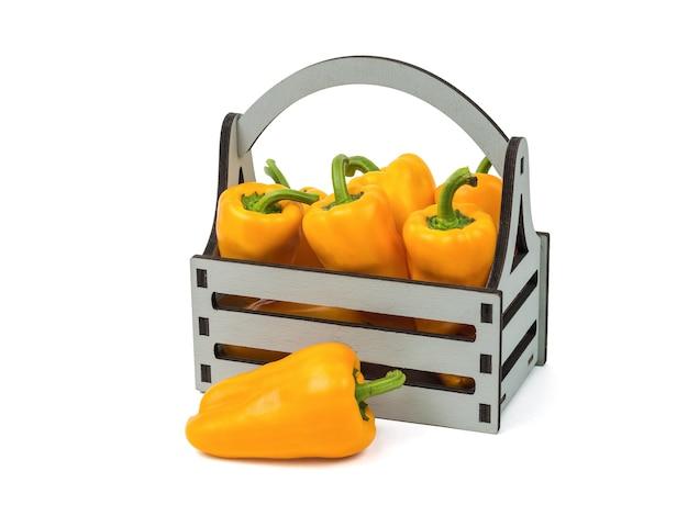 Boîte en bois avec poivron frais isolé sur fond blanc. la nourriture végétarienne.