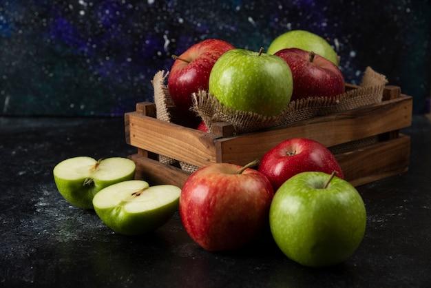 Boîte en bois de pommes biologiques fraîches sur une surface noire. .
