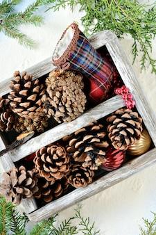 Boîte en bois avec des pommes de pin et des jouets de noël avec des branches de sapin sur un fond bleu clair