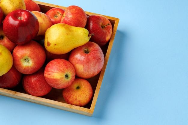 Boîte en bois avec pommes et poires sur studio bleu