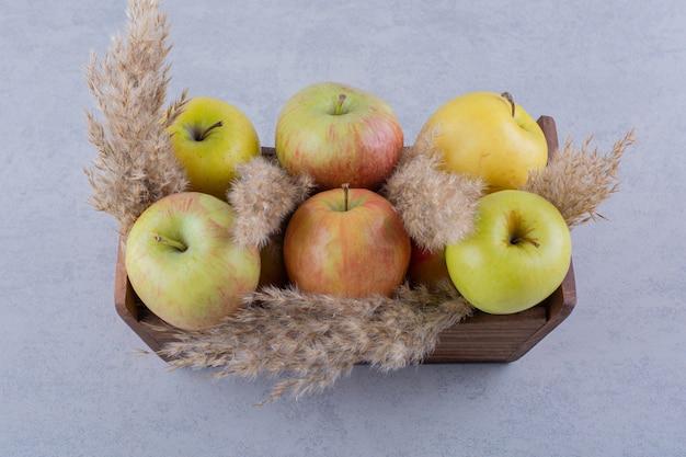 Boîte en bois de pommes vertes fraîches sur pierre.