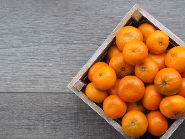 Boîte en bois remplie de mandarines. une mandarine pelée