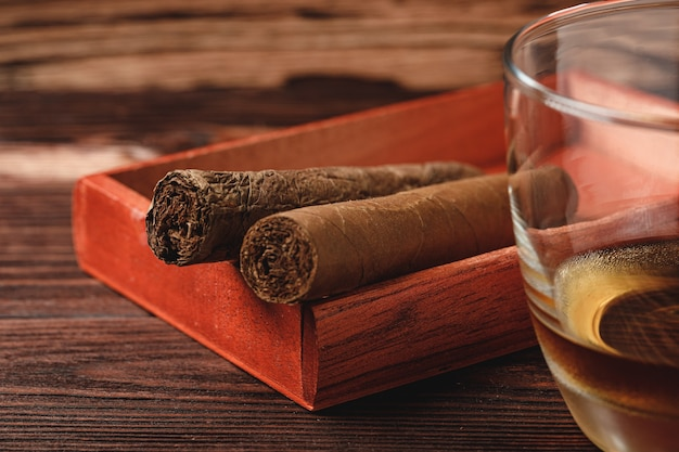 Boîte en bois rouge avec des cigares roulés sur table en bois se bouchent