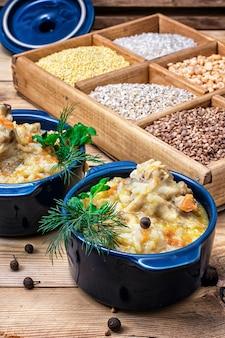 Boîte en bois avec des variétés de céréales sur le fond du pilaf cuit