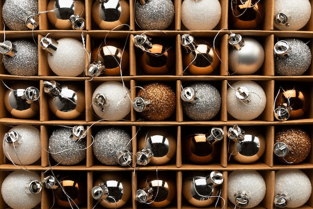 Une boîte de boules de noël sur un arbre de noël se bouchent