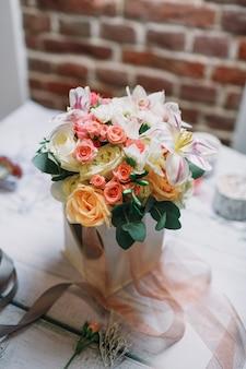 Boîte avec des bouquets blancs et oranges sur le travail de fleuriste