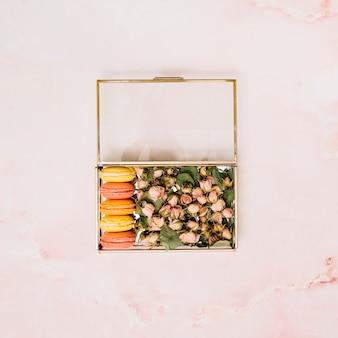 Boîte avec des boutons de fleurs et des biscuits sur une table lumineuse