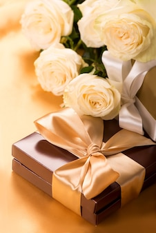 Boîte brune avec des bonbons et du ruban doré close up
