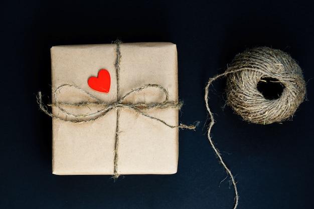Boîte cadeau artisanale enveloppée dans du papier craft avec coeur en bois rouge, corde et arc sur fond noir. vue de dessus, pose à plat