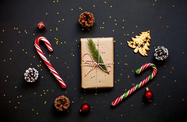 Boîte cadeau artisanale de noël avec des pommes de pin, des cannes de bonbon et des confettis